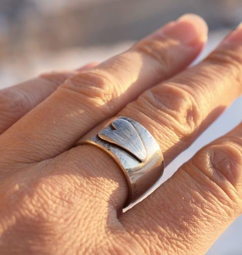 bred silverring med liggande hjärta på finger utomhus
