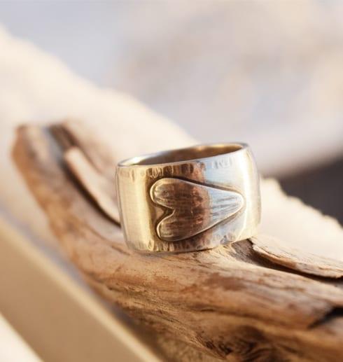bred silverring med liggande hjärta på träbit utomhus
