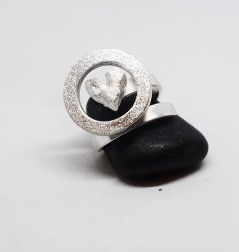 silverring på svart sten med vit bakgrund