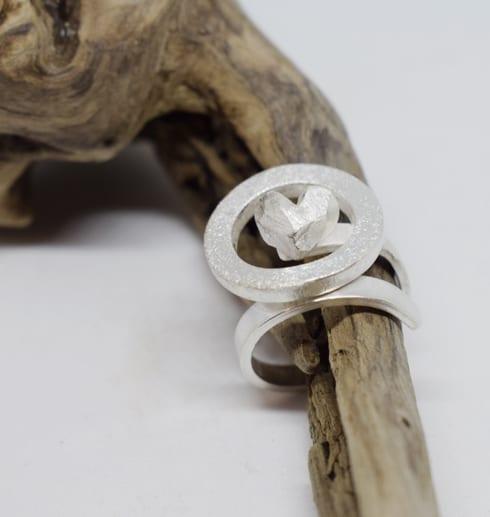 silverring med ring och hjärta på trädgren med vit bakgrund