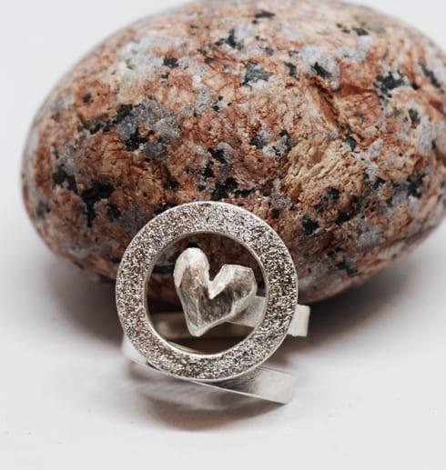 silverring med hjärta och ring med röd sten i bakgrunden
