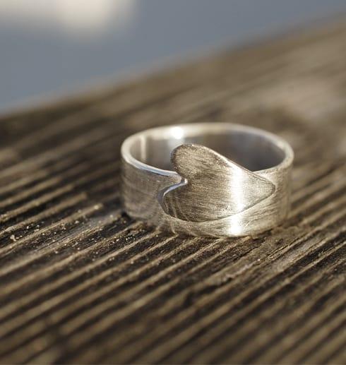 silverring med utsågat hjärta på träräcke utomhus