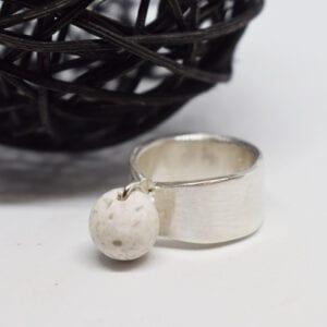 silverring med kula i marmor på vit bakgrund med svart trådboll bakom
