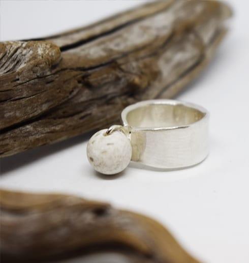 silverring med kula i marmor på vit bakgrund med trädgren bredvid