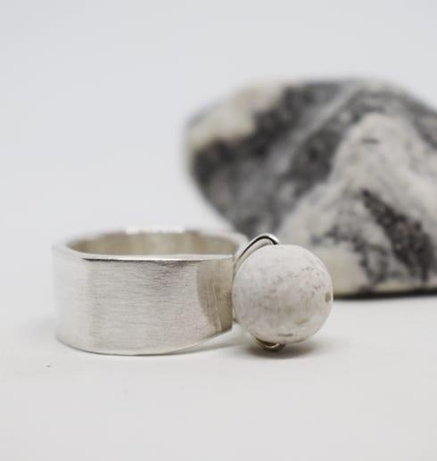 silverring med kula i marmor påv vit bakgrund med randig sten bakom