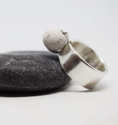 silverring med kula lutande mot grå sten