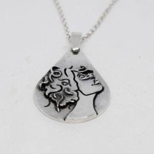 droppformat silversmycke med kvinnoansikte på vit bakgrund