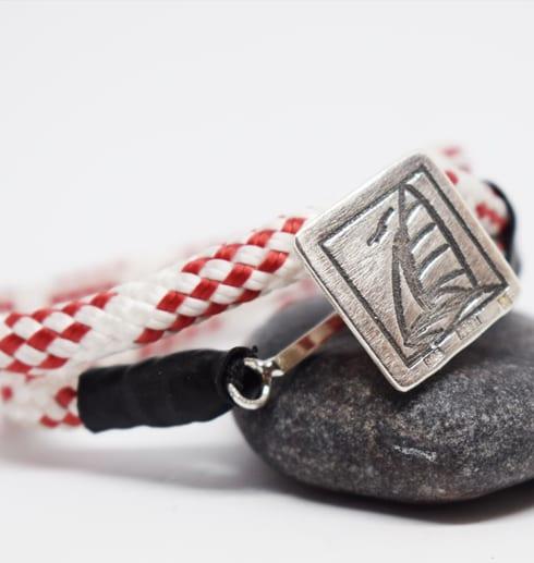 rödvit tamp med silverbricka med segelbåt på grå sten