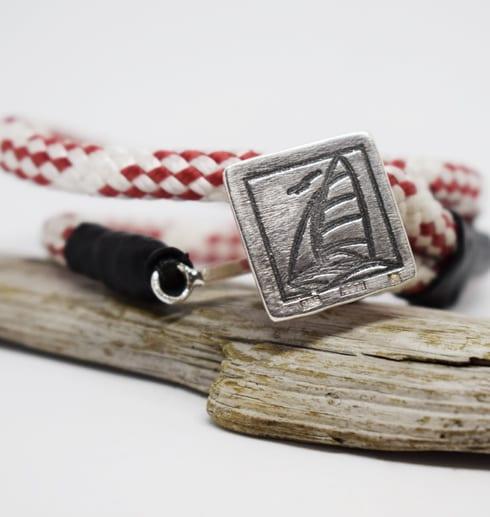 rödvitt armband med silverbricka med segelbåt på träbit