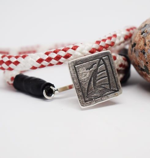 Rödvitt armband med silverbricka med segelbåt på vit bakgrund