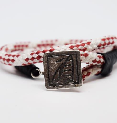 rödvitt armband med silverbricka med segelbåt på vit botten