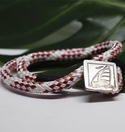 rödvitt armband med silverspänne med segelbåt med grönt blad bakom