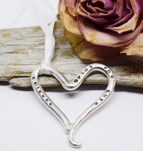 silverhjärta med text på träbit med ros bakom