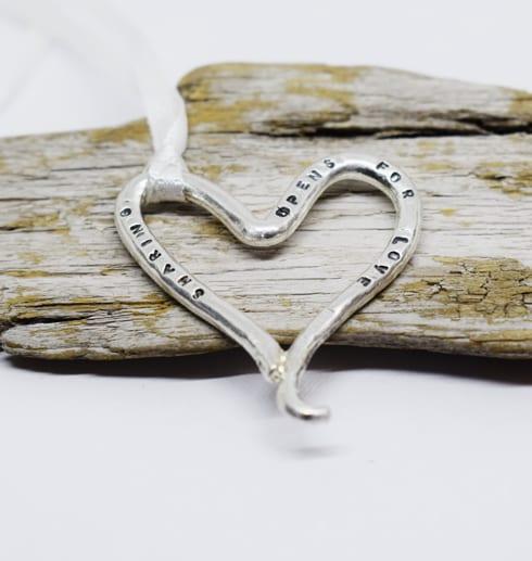 silverhjärta med text på träbit