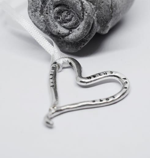 silverhjärta med textpå vit botten med betongros bakom