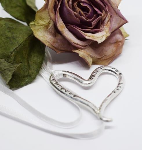silverhjärta på vit bakgrund med ros bakom