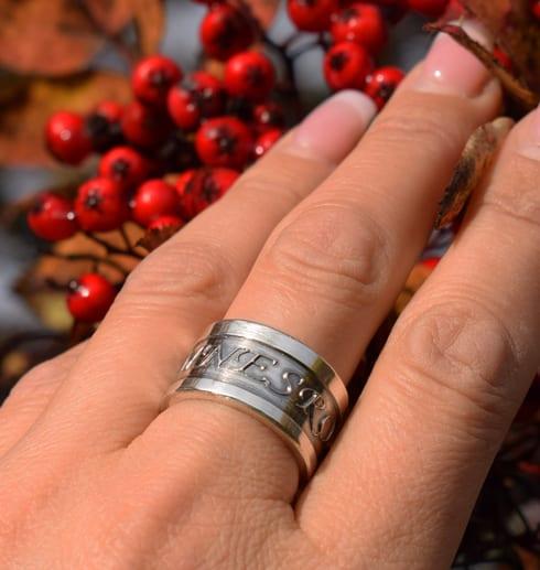 ring i silver på finger utomhus med rönnbär i bakgrunden