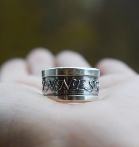 bred silverring med texten sinnesro i handflata utomhus