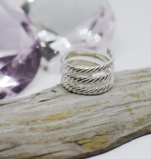 mönstrad spiralring på träbit med diamanter bakom
