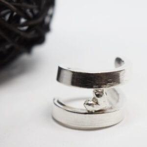 silverring med hjärta på vit botten med svart trådboll i ena kanten