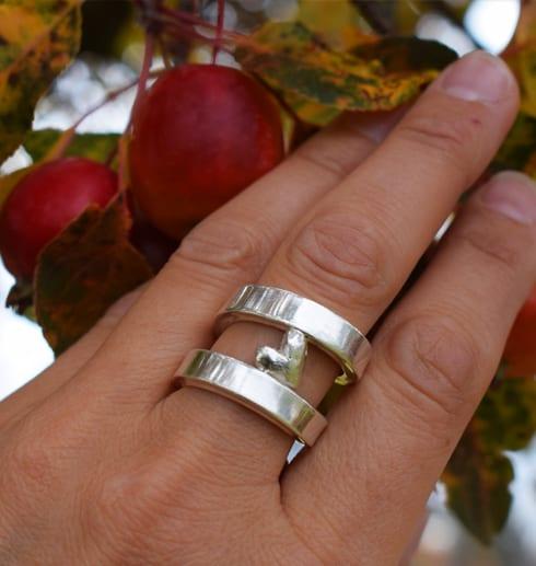 silverring med hjärta på finger mot äppelträd utomhus