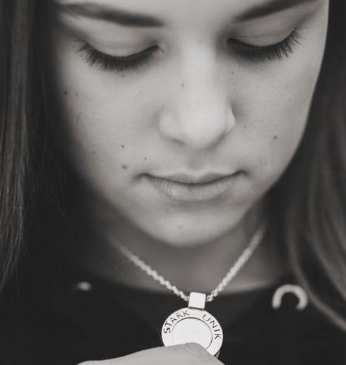 flicka med silverhalsband kring halsen utomhus