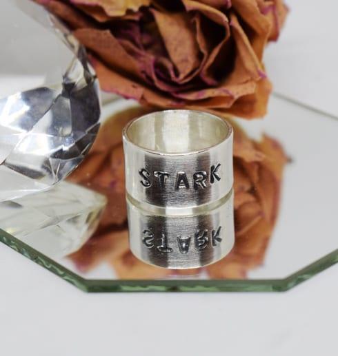 silverring med text på spegel med ros och diamant