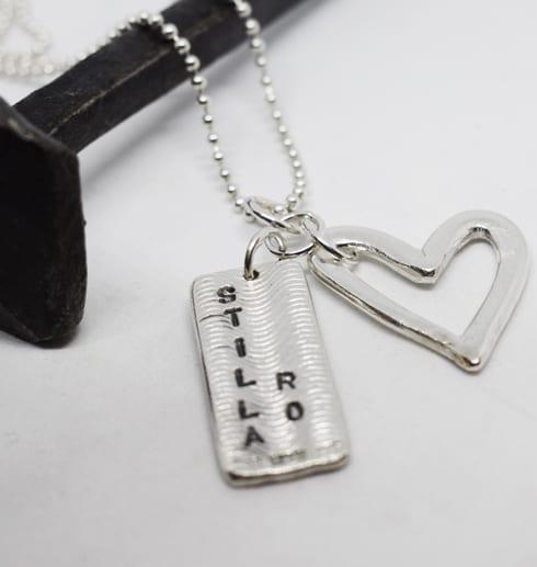 halsband med hjärta och platta på vit bakgrund med järnspik