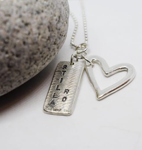 silverhalsband med hjärta och platta med texten stilla ro med vit sten