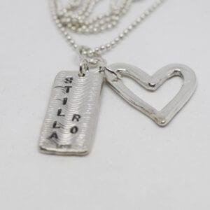 silversmycke med hjärta och platta med texten stilla ro på vit bakgrund