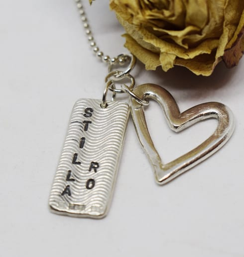 halsband med hjärta och platta med texten stilla ro i silver på vit botten med gul ros