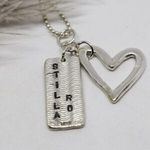 halsband med hjärta och platta i silver med texten stilla ro på vit botten med fjäder i bakgrunden
