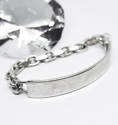 coolt silverarmband mot vit botten med stor diamant bredvid