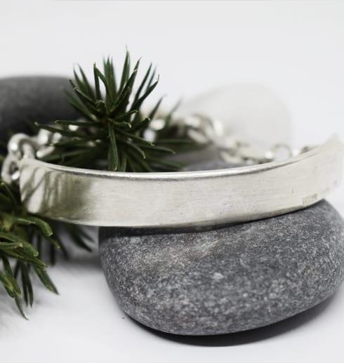 silverarmband på stenar med grankvist