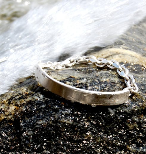 coolt silverarmband på stenar med havsvåg