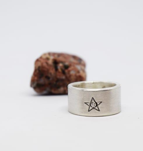silverring med stjärna på vit botten med röd sten bredvid