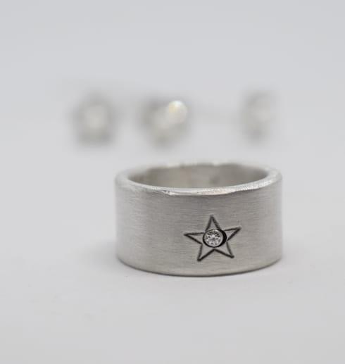 silverring med stjärna på vit botten med gnistrandehårspännen bakom