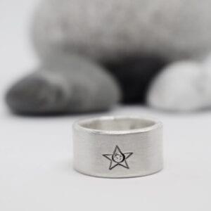 silverring med stjärna med stenar bakom
