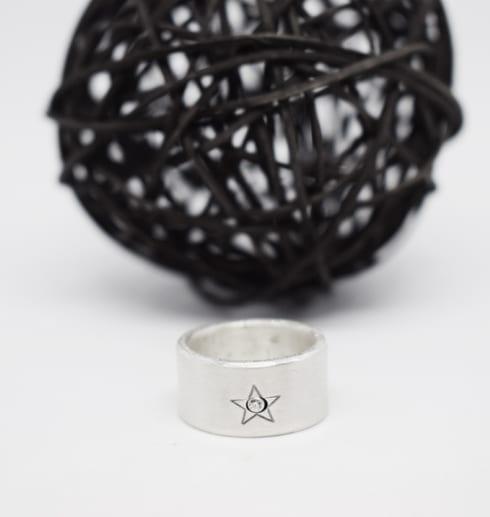silverring med stjärna mot vit botten och svart trådboll bakom
