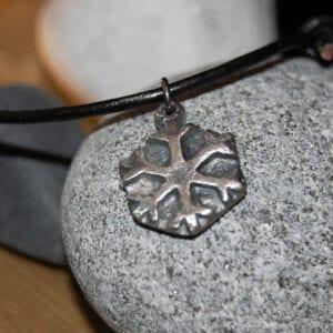 liten silverstjärna i läderrem på stenar