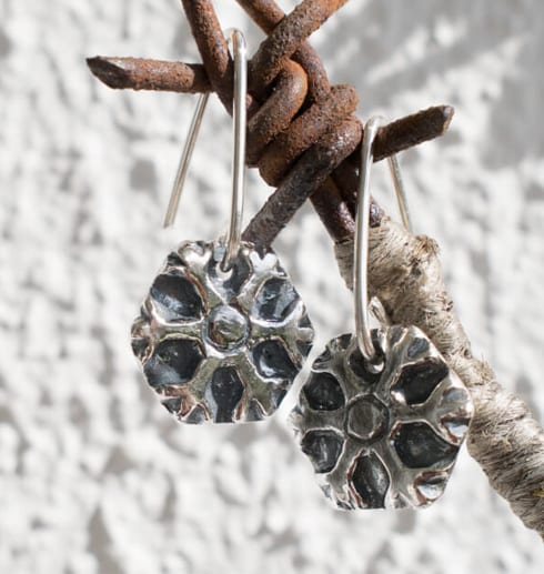 silverörhängen i form av snöflingor som hänger på rostig taggtråd