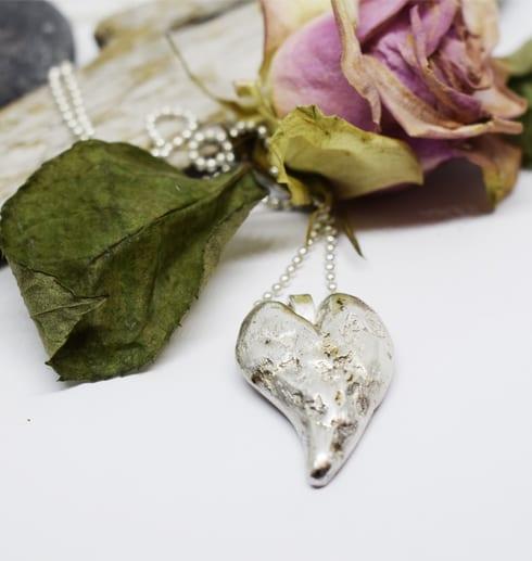 silverhjärta i kedja med ros och träbit bakom