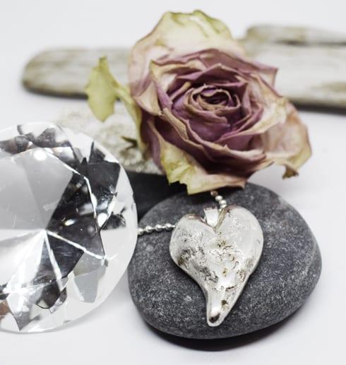silverhjärta på sten med ros och diamant bakom