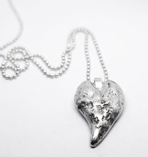 silverhjärta i kedja med vit bakgrund