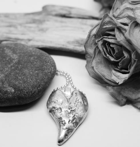 silverhjärta i kedja med sten, ros och träbit