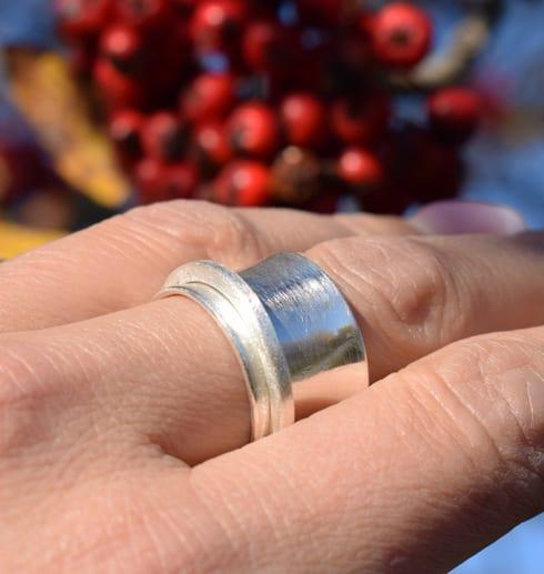 bred silverring på finger utomhus med rönnbär i bakgrunden