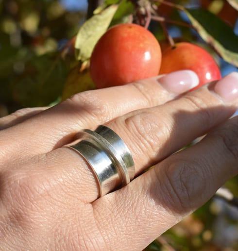 bred ring i silver på finger utomhus med äppelträd i bakgrunden