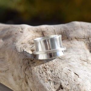 bred silverring på träbit utomhus
