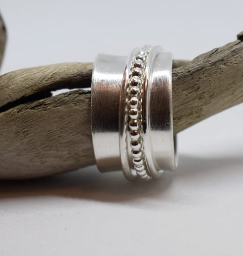 bred ring helt i silver på trädgren med vit bakgrund