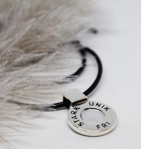 runt silversmycke med texten STARK, UNIK, FRI i läderrem med beige fjäder bredvid